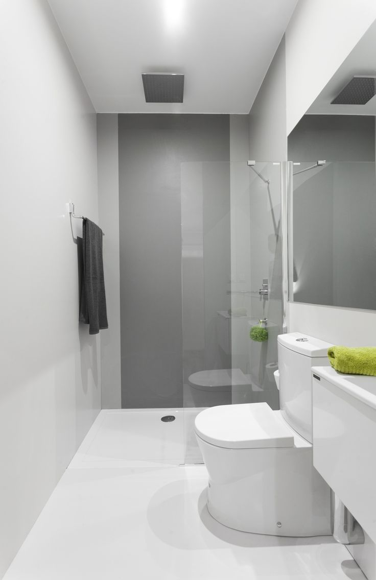 an ultra minimalist bathroom with a grey accent wall, sleek walls and a floor, white furniture and appliances and a statement mirror