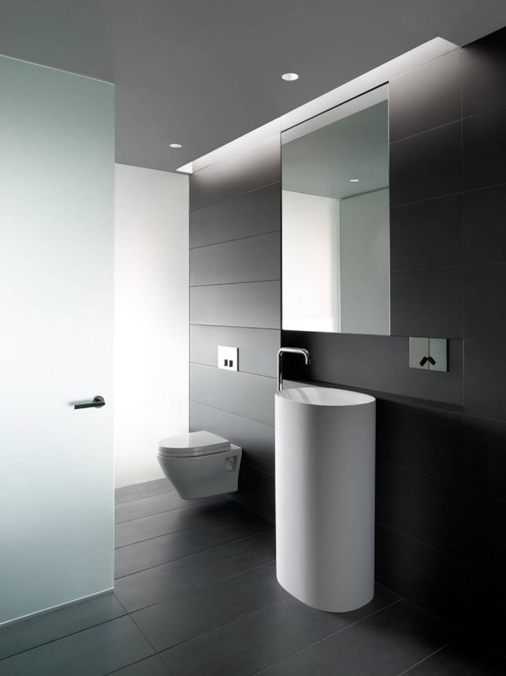 a dark minimalist powder room clad with long narrow tiles, a hidden storage unit and a frosted glass door
