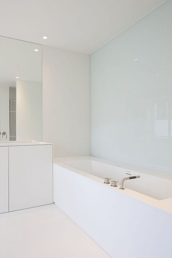 a white sleek minimalist bathroom with a glass wall, a statement mirror, white furniture and appliances
