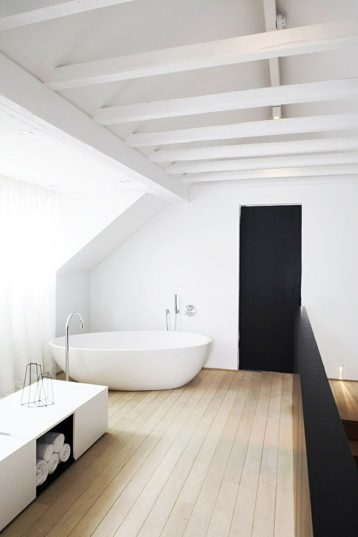 a contrasting minimalist bathroom with a white ceiling with beams, a white bathtub, a white bench with storage and a wooden floor
