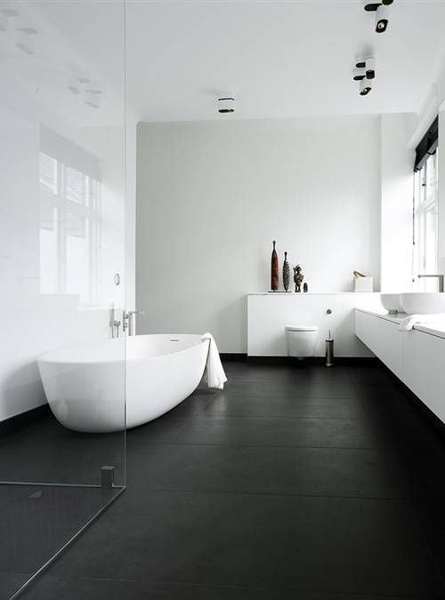 a contrasting bathroom with a black floor,  white walls, a long white vanity, several windows and black Roman shades, a seamless glass enclosed shower