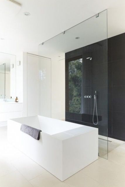 a minimalist bathroom with a black accent wall and all-white everything, white appliances and furniture
