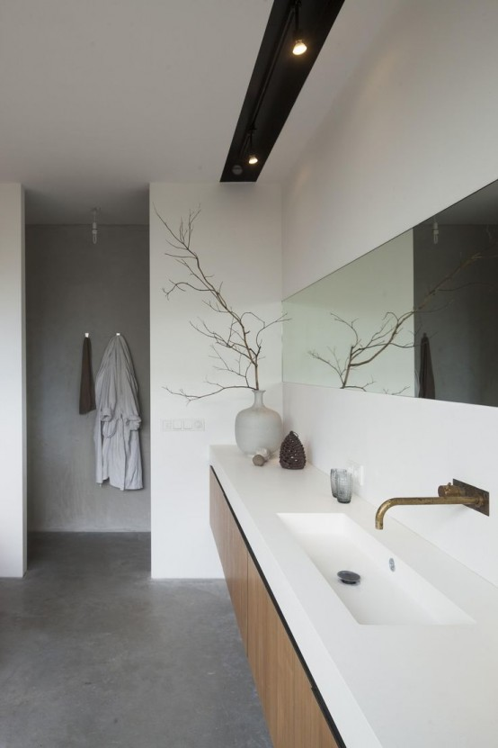 a minimalist bathroom done with white concrete, with a grey concrete floor, a long wooden vanity and a long and narrow mirror plus lights over it