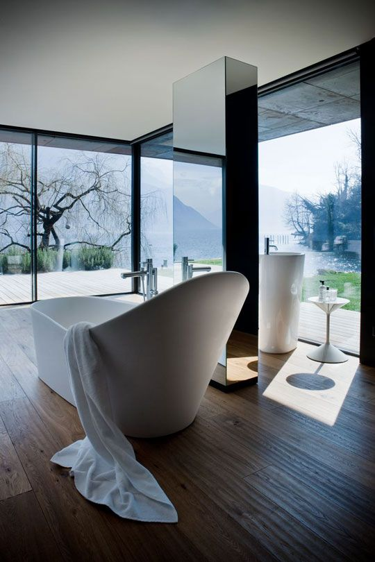 a chic glass enclosed minimalist bathroom with a wooden floor, white free standing appliances and a mirror pillar