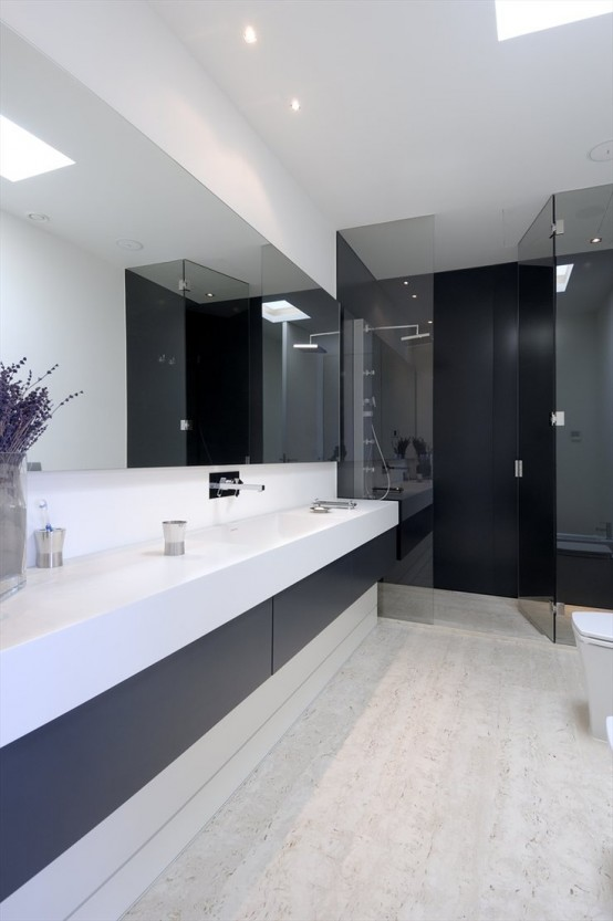 a minimalist contrasting bathroom with a long and sleek vanity in black and white, a statement mirror, a shower clad with dark glass