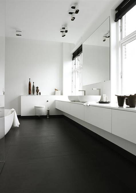a contrasting minimalist bathroom with a black floor, a long white vanity, a statement mirror, two windows and white furniture and appliances