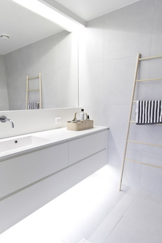 an ultra-minimalist white bathroom with a floating vanity with built-in lights, a statement mirror and a ladder for storing towels