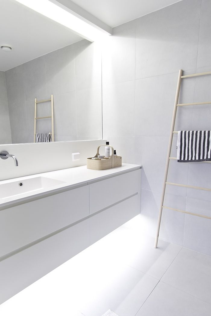 an ultra minimalist white bathroom with a floating vanity with built in lights, a statement mirror and a ladder for storing towels