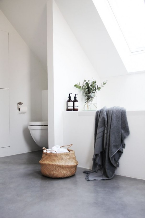 a minimalist attic bathroom with white walls and a ceiling, with a grey concrete floor, windows and white appliances