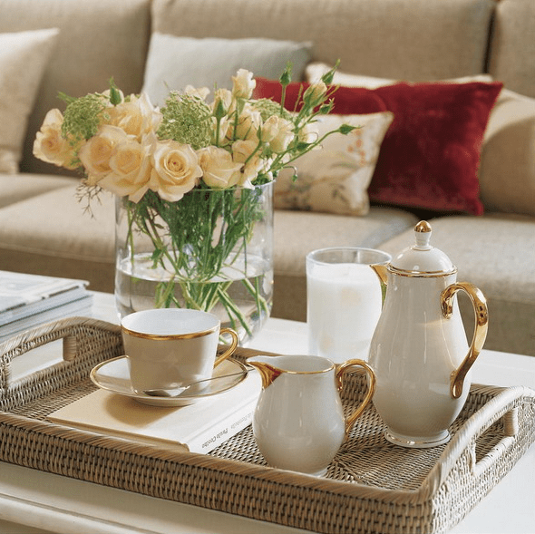 a white coffee table with a tray with elegant vintage coffeeware, a candle and a fresh bloom arrangement