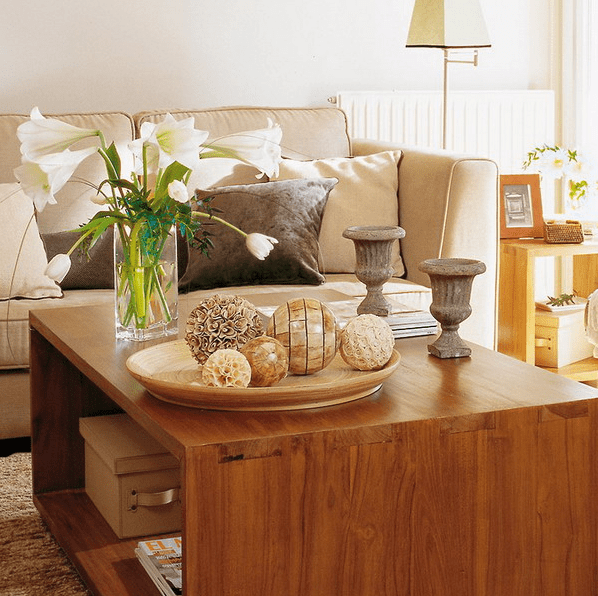 a sleek wooden coffee table with vintage urns, a floral arrangement, boxes and magazines