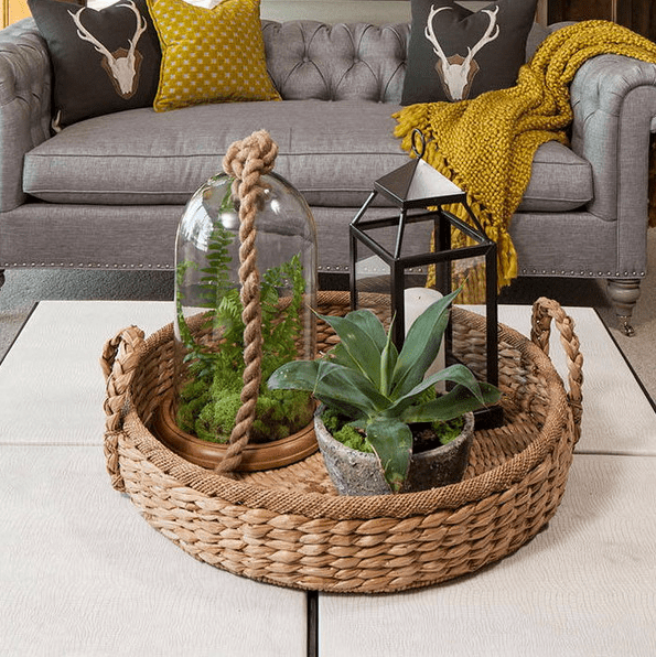 a basket tray with a terrarium, a candle lantern and a potted plant for a boho chic feel