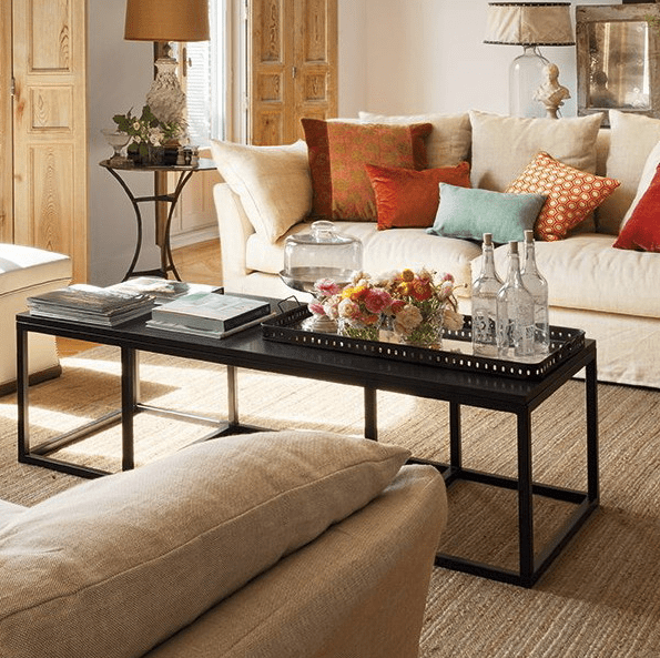 a long and narrow black coffee table with books and magazines and a mirror tray that features bright floral arrangements and bottles