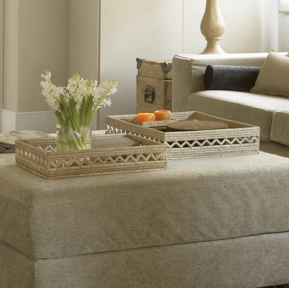 an upholstered ottoman that doubles as a coffee table and features two woven trays and fresh blooms and candles