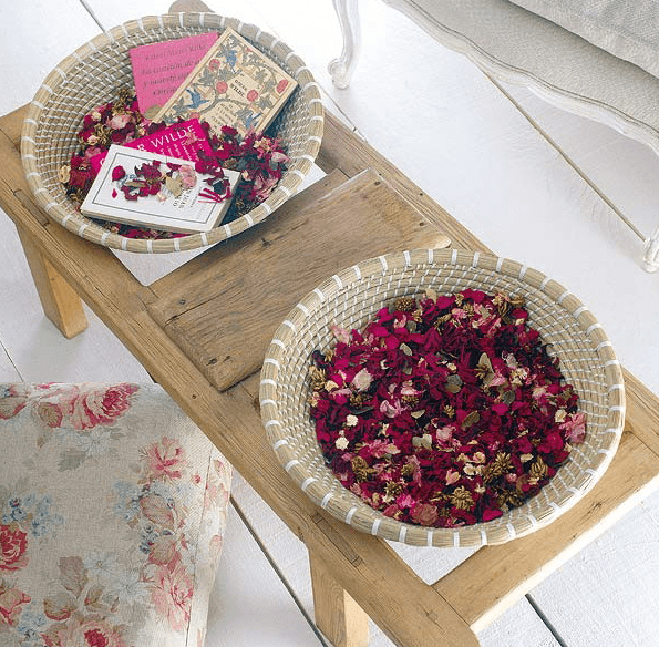 a wooden coffee table with baskets filled with colorful petals and some books is a very dreamy idea
