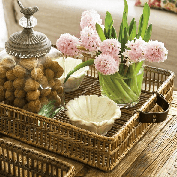 a rustic wooden coffee table with a woven tray, some pink blooms and a jar with nuts for decor