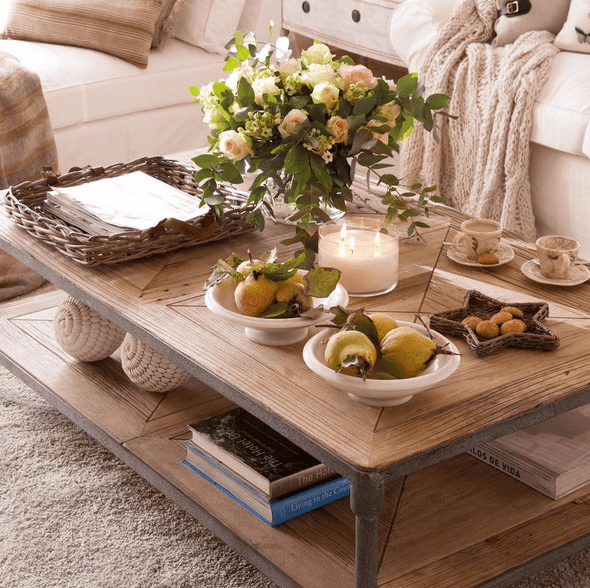 a rustic two tier coffee table with books, fruits, a fresh floral arrangement and a large candle