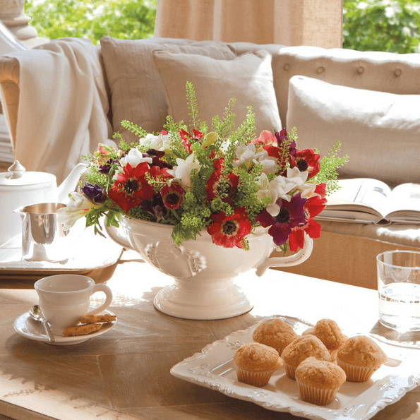 beautiful coffee table styling with a bright floral centerpiece, coffeeware and tasty cupcakes