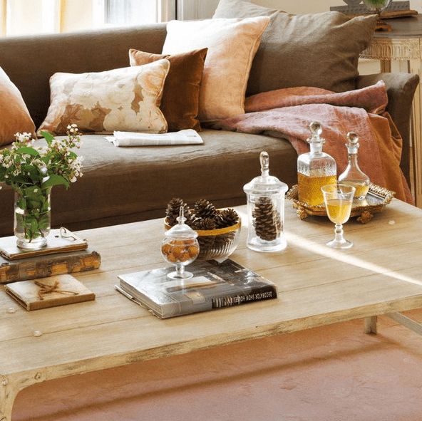 a light colored wooden coffee table with pinecone arrangements, books, greenery and alcohol in chic glassware
