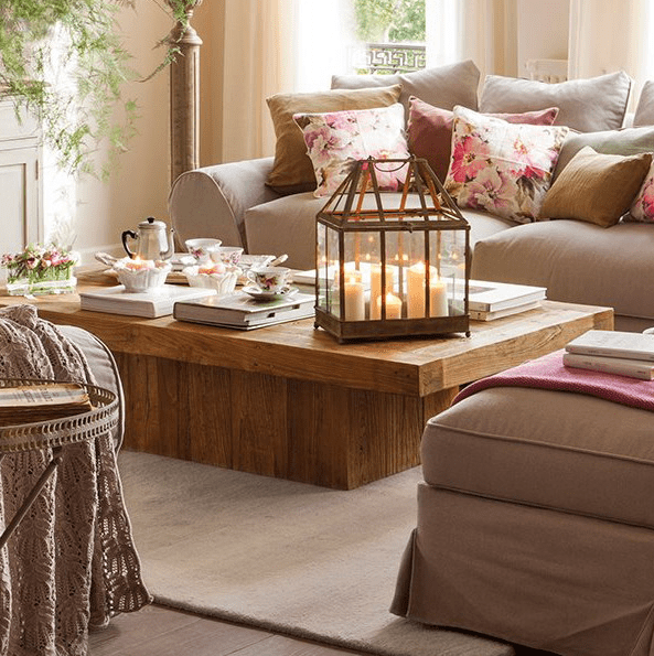 a rustic wooden coffee table with a large candle lantern, some vintage teacups, books and fresh blooms