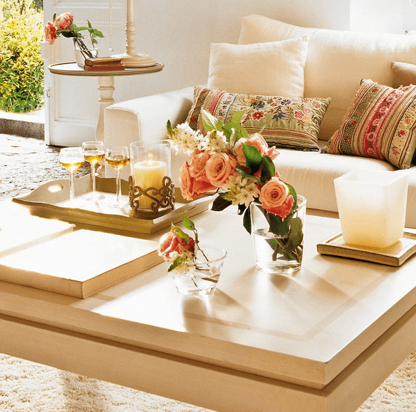 a contemporary coffee table with some fresh blooms, books, a candle and fresh wine
