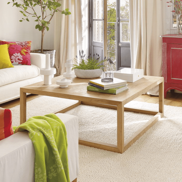 a contemporary coffee table with some books, candles and potted blooms for a clean and airy feeling