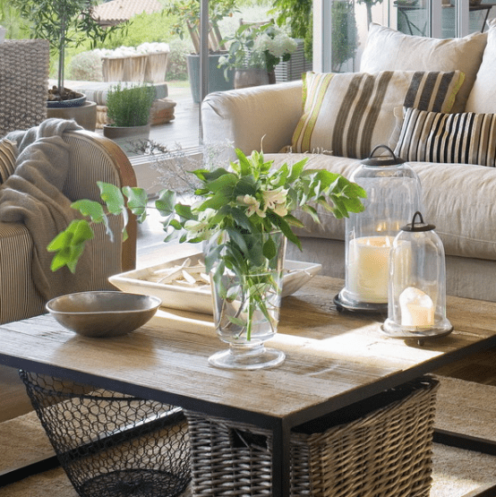 a wooden coffee table with candle lanterns, a greenery and floral arrangement, a tray with starfish for a coastal feel