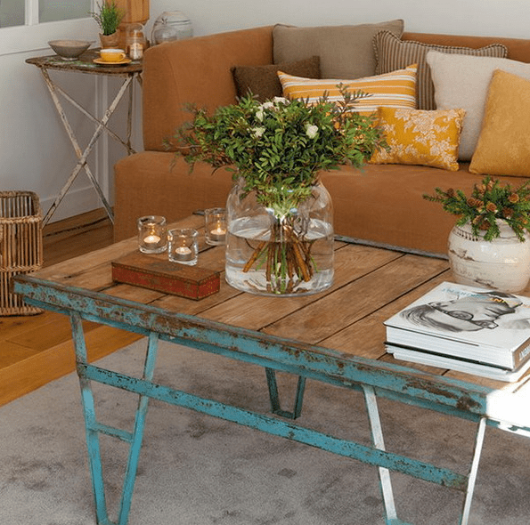 a shabby chic coffee table with a wooden top, fresh greenery and blooms and just some candles