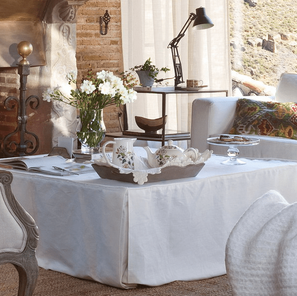 a large coffee table with a white tablecloth, a tray with teaware and some fresh blooms for a cute look