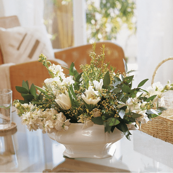 a vintage white porcelain bowl with fresh white blooms and greenery for decorating a coffee table