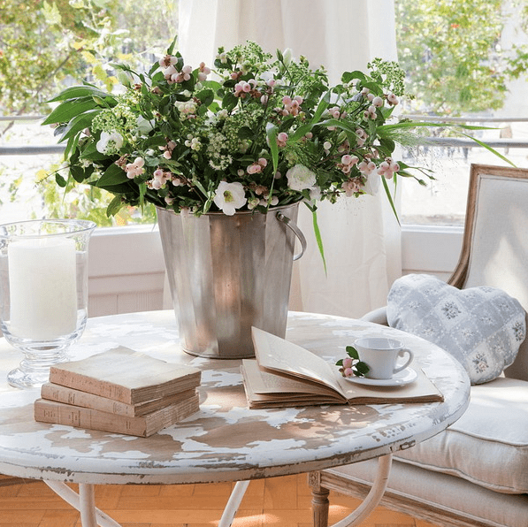 a round shabby chic coffee table with books, an oversized candle in a clear glass vase, a metal bucket with greenery and blooms