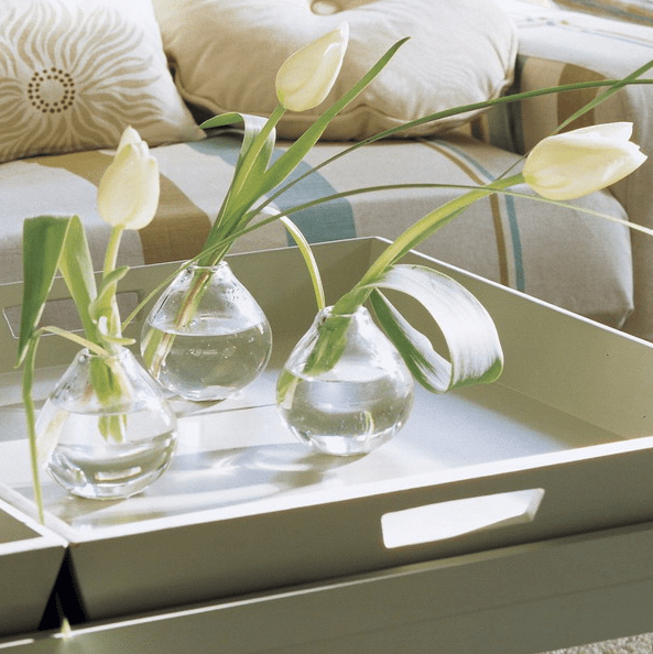 a white tray with clear vases and white tulips for contemporary chic as it is