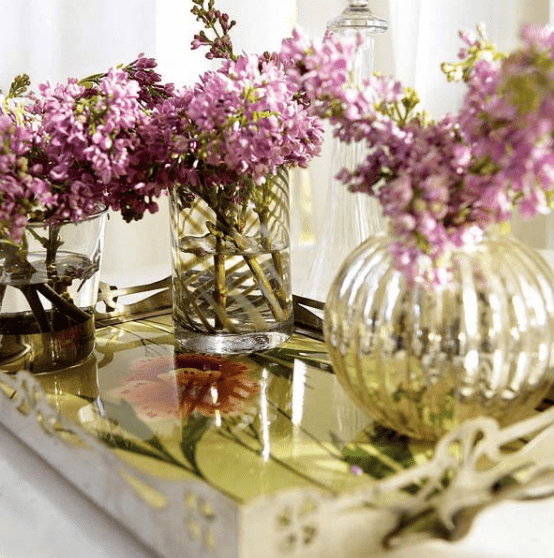 a coffee table with a tray and bright floral arrangements in clear vases is a very chic and cool idea