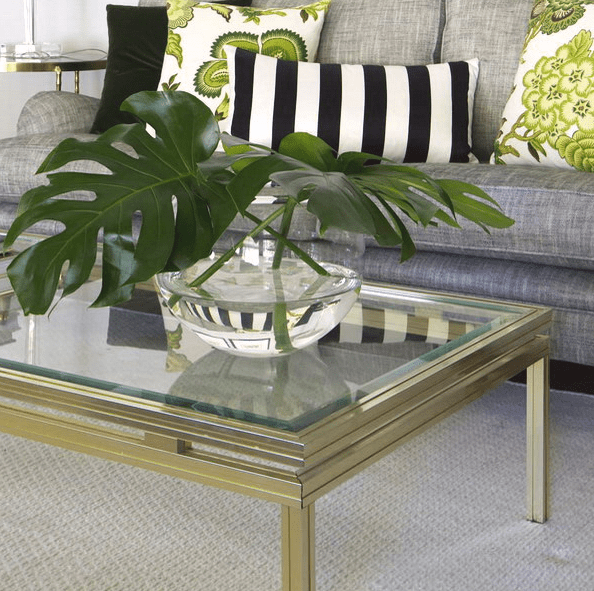 a gold frame coffee table with a glass top and a large clear glass with greenery
