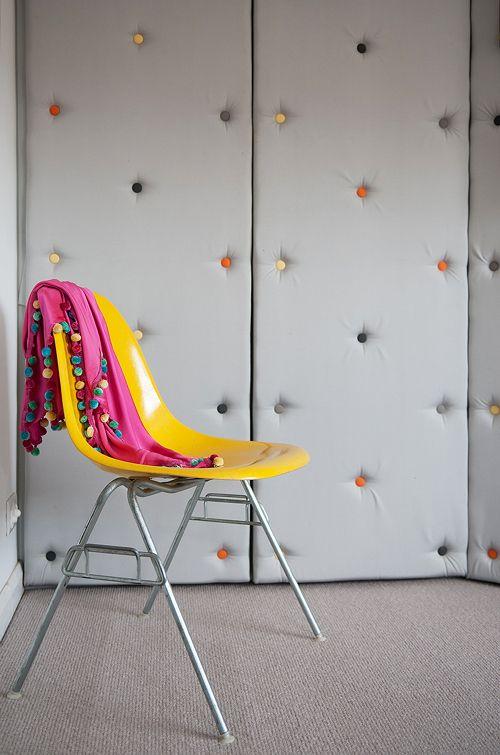 upholstered grey walls with colorful decorative nails make the space ultra-modern and playful