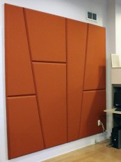 a soundproofing wall done with asummetrical rust-colored wall panels