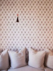 an upholstered tufted wall in blush isn't only a catchy decor feature but also a cool soundproofing idea