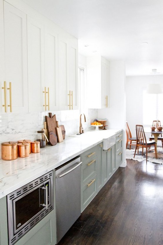 a light green and white mid-century modern kitchen with marble countertops and a backsplash plus gold touches