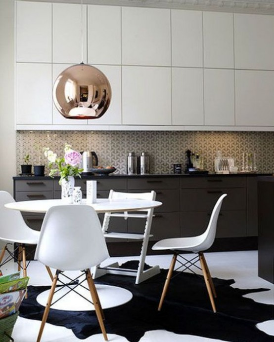 a black and white mid-century modern kitchen with a white dining set, a mosaic tile backsplash and a large copper lamp