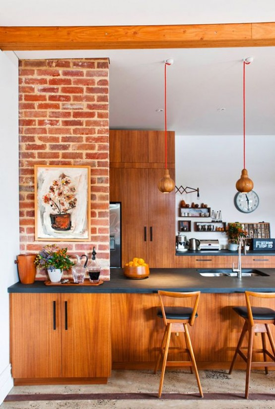 a bright mid-century modern kitchen with reddish furniture, pendant lamps, black countertops and artworks