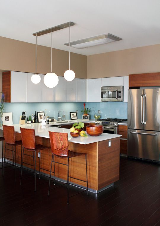 a rich-stained and white mid-century modern kitchen with a blue backsplash, metal appliances, pendant lamps