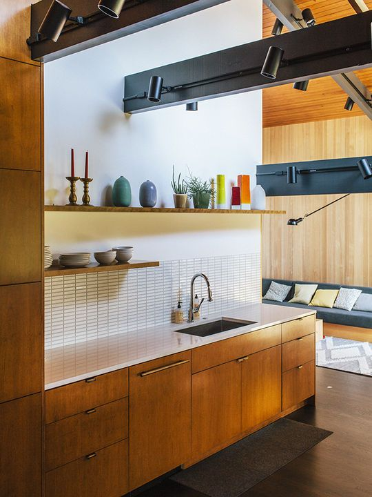 a mid-century modern meets contemporary kitchen with light-colored wooden cabinets, a white tile backsplash, dark beams