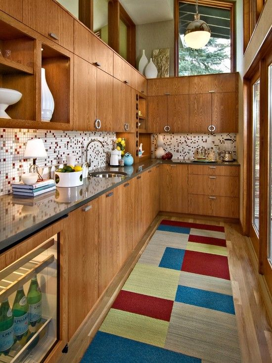 a rich-stained kitchen with a mosaic tile backsplash, a bright color block rug and skylights