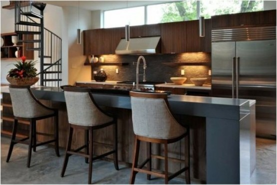 a stained wooden kitchen island with metal appliances, a raised countertop for eating and comfy stools