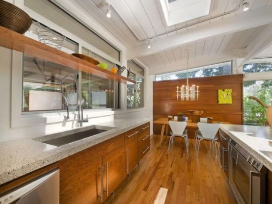 a mid-century modern kitchen wooden cabinets and stone countertops, w indow backsplash and skylights for more natural light