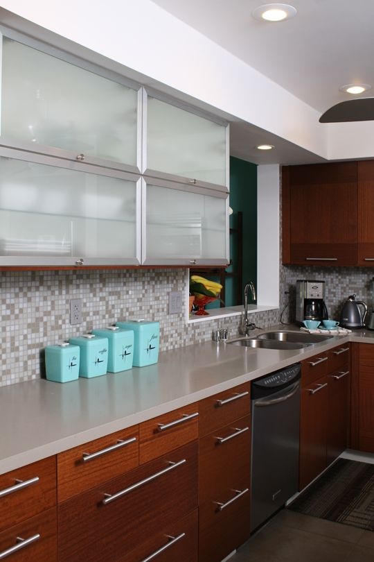 a mid-century modern kitchen with frosted glass and wood cabinets, a neutral countertop and mosaic tile backsplash