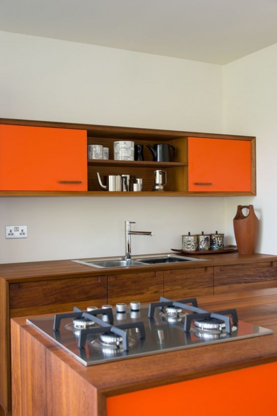 a mid-century modern kitchen with rich-stained wood and bright orange cabinets, metal appliances