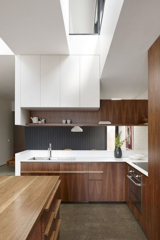 a mid-century modern meets minimalist kitchen with rich-stained and white cabinets, white countertops and a large wooden kitchen island