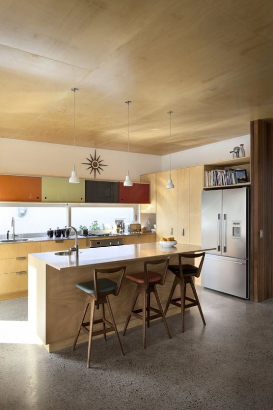a light colored plywood mid-century modern kitchen with muted colored cabinets, pendant lamps and stools