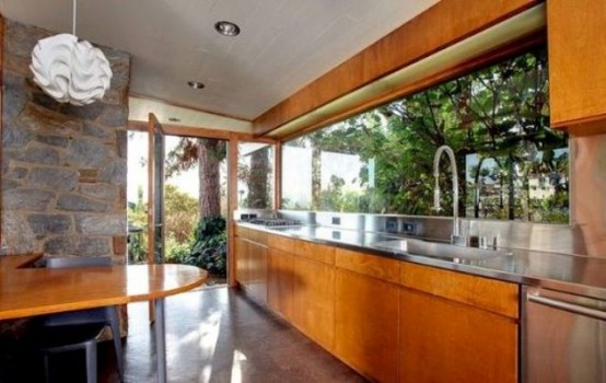 an orange mid-century modern wooden kitchen with metal countertops, a window backsplash and a matching table